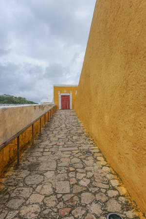 Izamal, Yucatán, Mexico: A red door at the end of a ramp on the exterior of the Franciscan Monastery and Convent of San Antonio de Padua, built in 1561. Stock fotó