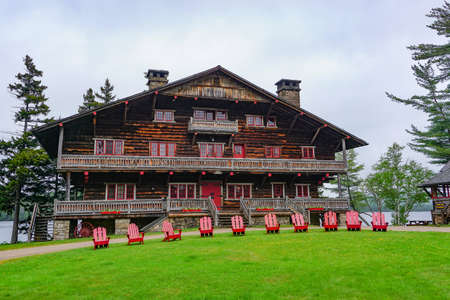 Sagamore Lake, NY: A row of Adirondacks chairs on the lawn in front of the Main Lodge at the Great Camp Sagamore, built in 1897.