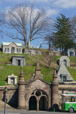 Brooklyn, New York: A trolley waits for passengers below obelisks and mausoleums on a hillside in a section of historic Green-Wood Cemetery, founded in 1838.