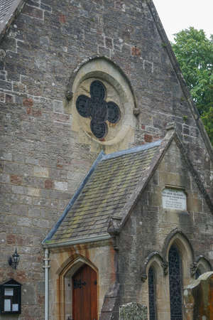 Luss, Scotland: Detail of the Luss Parish Church (1875) including the dedication plaque and stained-glass window.