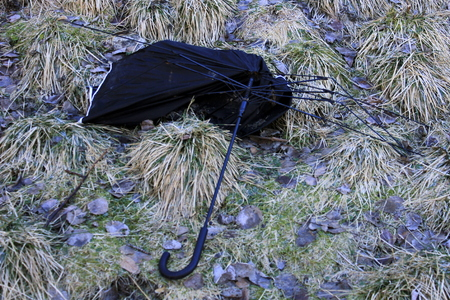 blown away: Wasted umbrella on sunny ground Stock Photo
