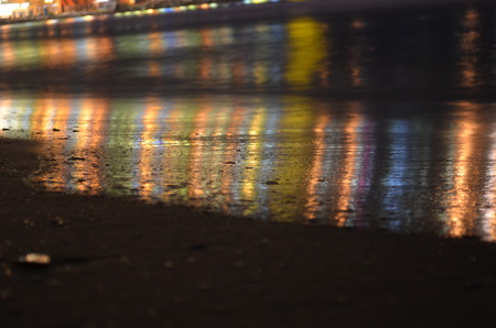 topsail: Reflection of night city lights in the sea wave Stock Photo