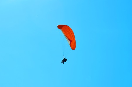 paraglider: Paraglider soaring in a cloudless blue sky Stock Photo