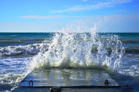 Powerful waves of the sea foam, breaking the concrete pier