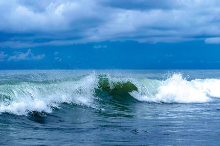Coastal transparent sea crashing wave with foam on its top