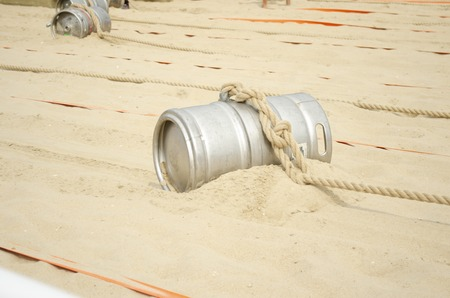 Sports competition with a barrel and a rope on the beach.