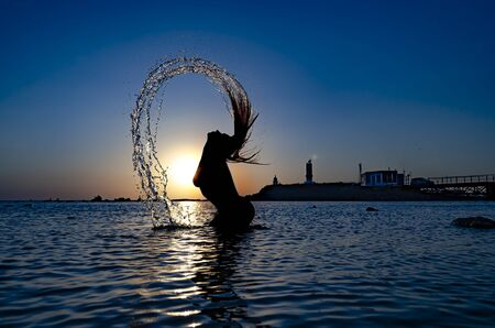 The silhouette of a sporty girl who hair makes water splashes on the sea when the sun goes down. 版權商用圖片