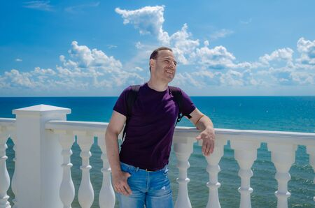 A healthy elderly man of athletic build stands near a white fence with balusters and looks at the blue sea.