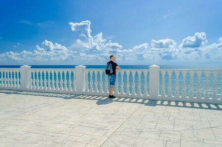 A healthy elderly man of athletic build stands near a white fence with balusters and looks at the blue sea. 版權商用圖片 - 130779591