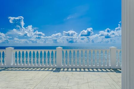 Terrace with white balusters to amazing views of the sea, sky and white clouds. Summer Tropical Background.