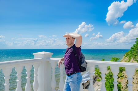 A healthy elderly man of athletic build stands near a white fence with balusters and looks at the blue sea. 版權商用圖片 - 130781671