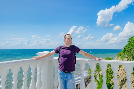A healthy elderly man of athletic build stands near a white fence with balusters and looks at the blue sea. 版權商用圖片 - 130781672