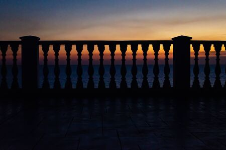 Beautiful seascape and fence with old classic white balusters, The evening sun shines through the space of the balustrade columns make light and shadow go down to the ground.