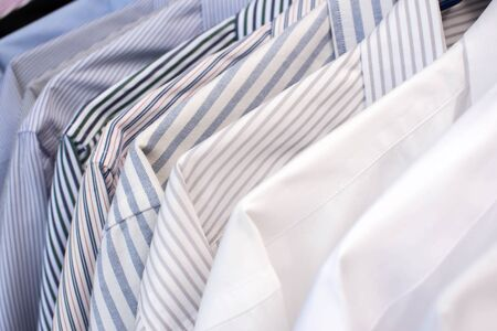 Men shirts hanging on rack in a row, Selective Focus