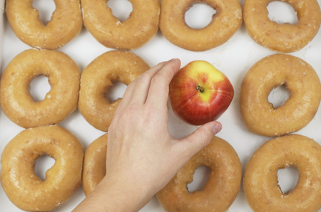 Hand Choosing a Healthy Organic Apple in the Midst of A Dozen Iced Donuts, Healthy Versus Unhealthy