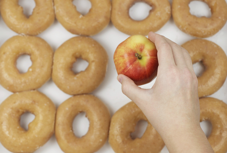 Hand Choosing Organic Fresh Apple Over Krispy Creme Donuts
