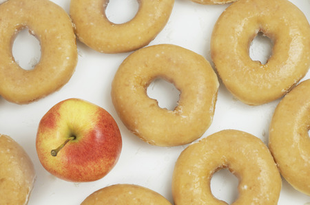 Healthy Organic Apple in the Midst of Iced Donuts, Healthy Versus Unhealthy Banco de Imagens