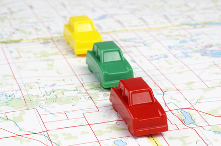 Red, Yellow, and Green Plastic Miniature Cars Traveling On A Road On A Travel Map