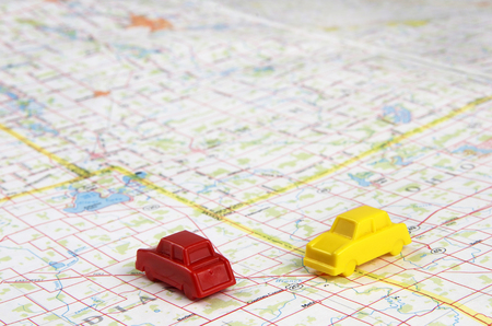 Red And Yellow Miniature Plastic Cars Intersecting On a Travel Map