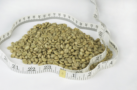 Green Raw Coffee Beans in Pile Surrounded By Cloth Tape Measure