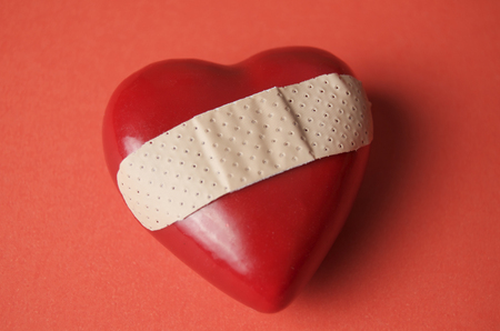 Red Heart on Red Background, Broken With Bandage Across Stock Photo