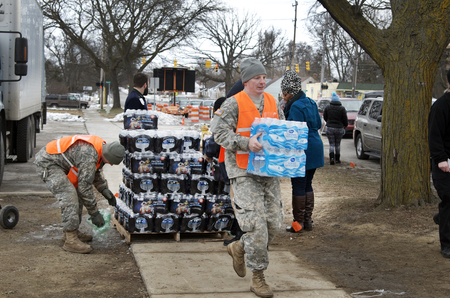 Flint, Michigan January 23, 2016: National Guard distributing bottled water to residents of Flint. January 23, 2016, Downtown Flint, Michigan, USA Banco de Imagens - 77553887