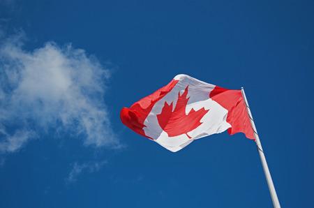 Canadian National Flag Waving Against A Blue Sky Imagens