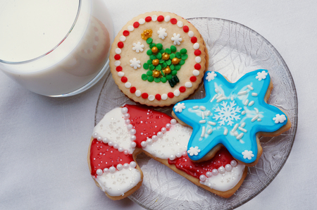 Artistically Decorated Christmas Cut-Out Cookies On Glass Plate With Glass Of Milk, White Background