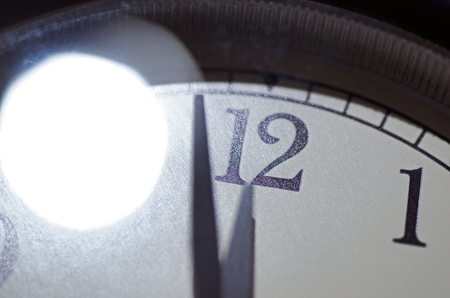 Doomsday Clock Set At Two Minutes Till Midnight With Bright Light Reflected On Glass Face
