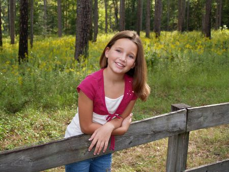 Young girl in pink leaning on a board fence.     photo