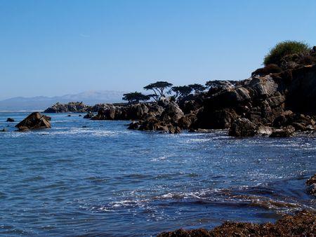 Rocky coast beneath a clear blue sky south of Santa Barbara, California    Stock Photo