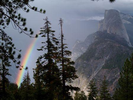 phenomena: A rainbow in the fog beside half dome in Yosemite National Park, California.