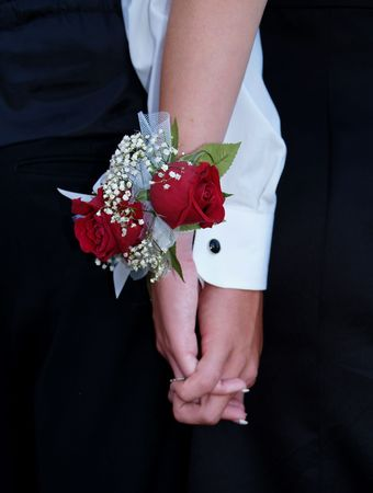 Red rose wrist corsage with babies breath and blue and white ribbons.