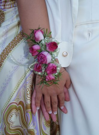 cuff link: Pink rose wrist corsage with babies breath and green and white ribbons.   Stock Photo