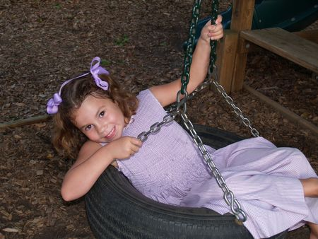 Young girl smiling and swinging on a tire swing.