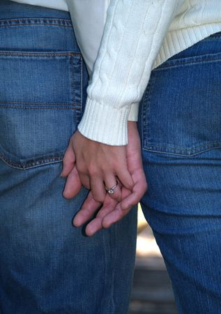 hands off: Couple holding hands showing off her engagement ring.       Stock Photo