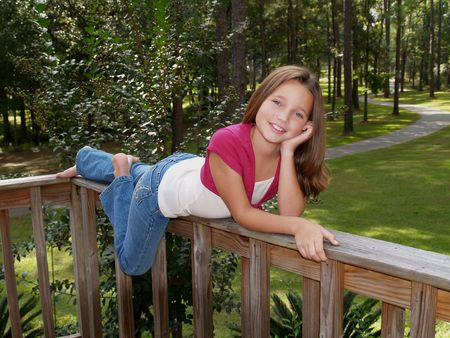 Young girl in denim and pink, laying of deck railing.