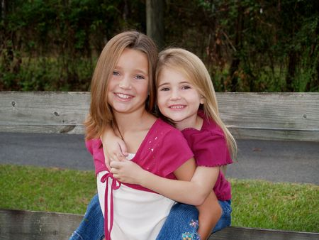 preteen girl: Two sisters in pink in front of a board fence.       Stock Photo