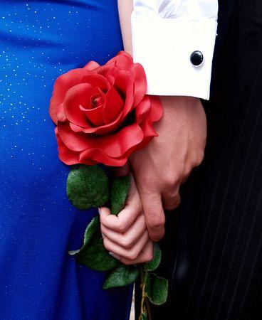 punos: Mayor mano y una rosa Foto de archivo