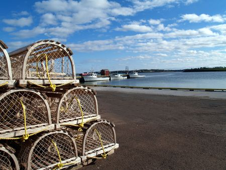 lobster boat: Lobster traps stacked on the wharf with fishing boats and harbor in the background and space for copy.