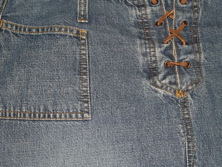 Close-up view of denim pants or skirt with laces up the front and pocket.      photo