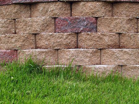 retaining: Green grass alongside multi-colored blocks on a retaining wall.
