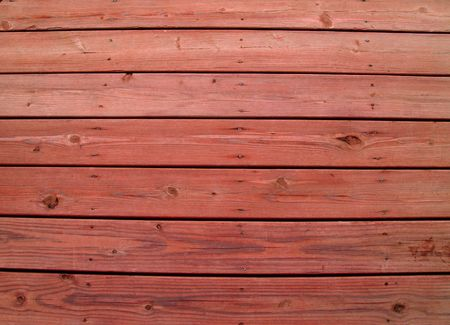 treated board: Wooden slats on a weathered wooden deck with redwood stain.