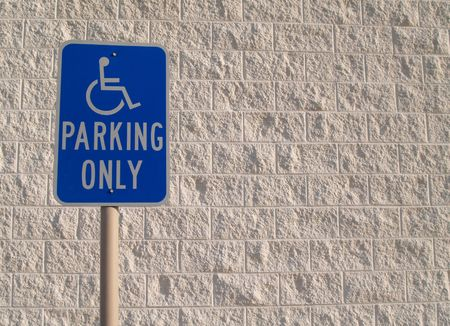 concrete block: Blue handicap parking sign with a white textured concrete block background that can be used for copy space.