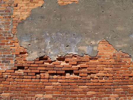 Old weathered wall with red multi-sized brick and a patched area.     photo