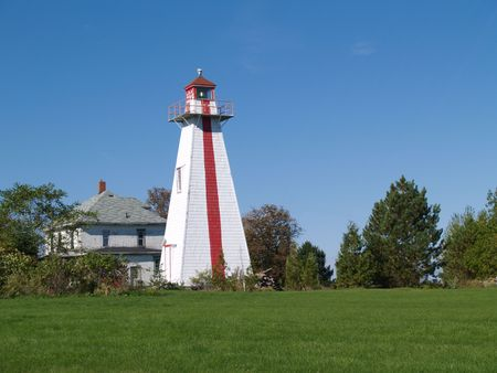 guiding light: Red and white lighthouse on Prince Edward Island, Canada beside an old house,