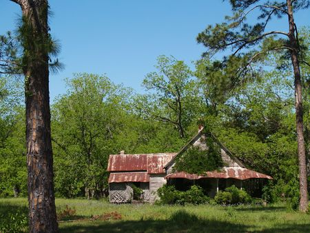 Old weathered, abandoned, historic home in south Georgia with a tin roof that is close to falling down.        写真素材