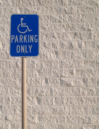 Blue handicap parking sign with a white textured concrete block background that can be used for copy space.      photo
