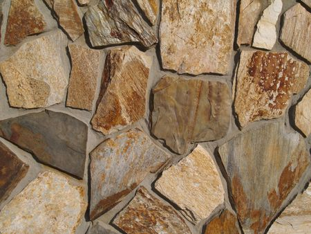 wall texture: Close-up of Multi-colored flat stone facade on a building.     Stock Photo