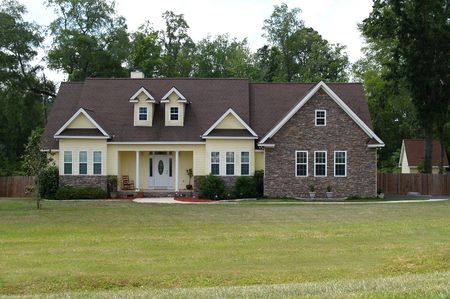 single dwellings: One story residential home with both brick and board siding on the facade.